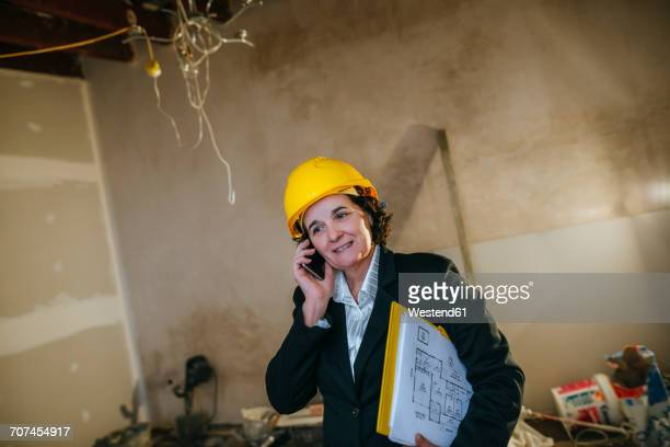 Woman wearing hard hat talking on phone on construction site