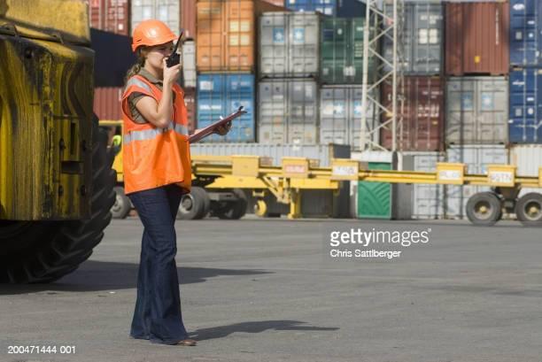 Woman wearing hard hat using walkie-talkie at container terminal