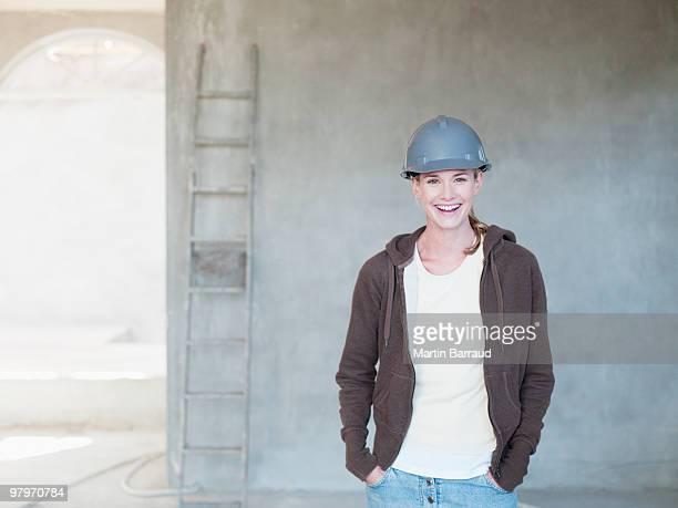 Woman wearing hard-hat inside house under construction