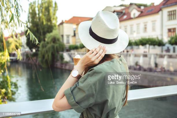 woman wearing hat against canal in city - ljubljana stock pictures, royalty-free photos & images