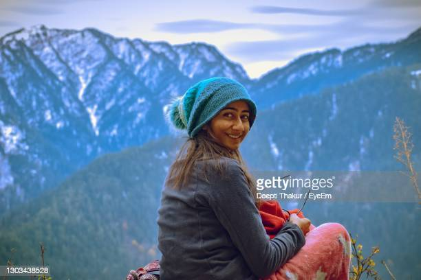 woman wearing hat against mountains during winter - wool stock pictures, royalty-free photos & images