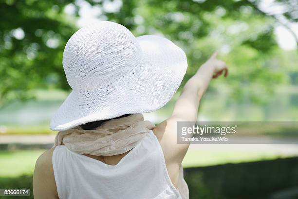 A woman wearing hat and pointing