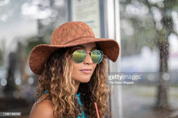 woman wearing hat and sunglasses while standing outdoors in city - sunglasses stock pictures, royalty-free photos & images