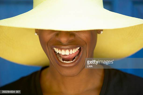 Woman wearing hat covering eyes, smiling
