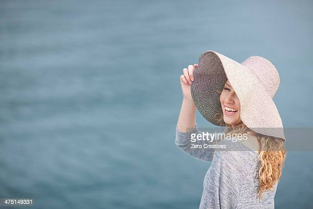 woman wearing hat enjoying sea - drooping stock photos and pictures