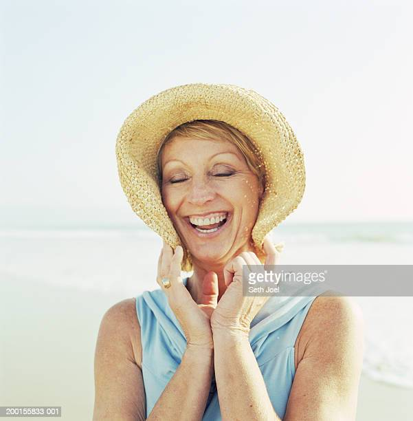 Woman wearing hat on beach, laughing