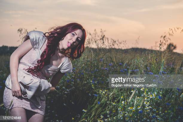woman wearing hat on field against sky during sunset - bogdan negoita stock pictures, royalty-free photos & images
