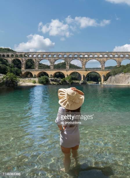 woman wearing hat standing in gardon river by pont du gard in vers-pont-du-gard, france - pont du gard stockfoto's en -beelden