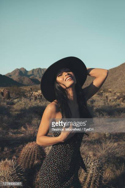 woman wearing hat standing on mountain against sky - southwest stock pictures, royalty-free photos & images