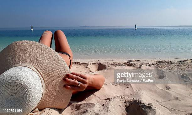 woman wearing hat while lying on sand at beach against sky - abu dhabi stock pictures, royalty-free photos & images