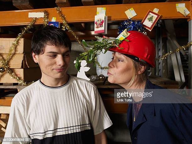 Woman wearing hat with misletoe branch trying to kiss young man in warehouse