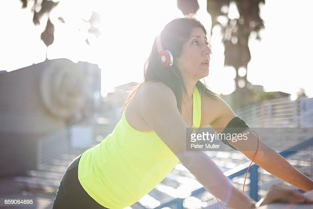 Woman wearing headphones and activity tracker doing standing push ups looking away