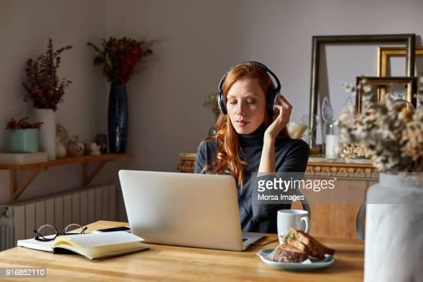 woman wearing headphones and using laptop at home - hygge stock pictures, royalty-free photos & images