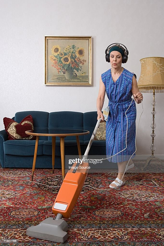 Woman wearing headphones and vacuuming : Stock Photo