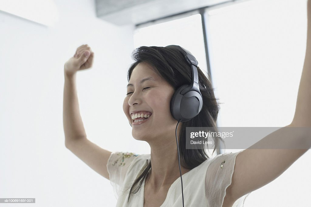 Woman wearing headphones, laughing with arms raised : Stockfoto