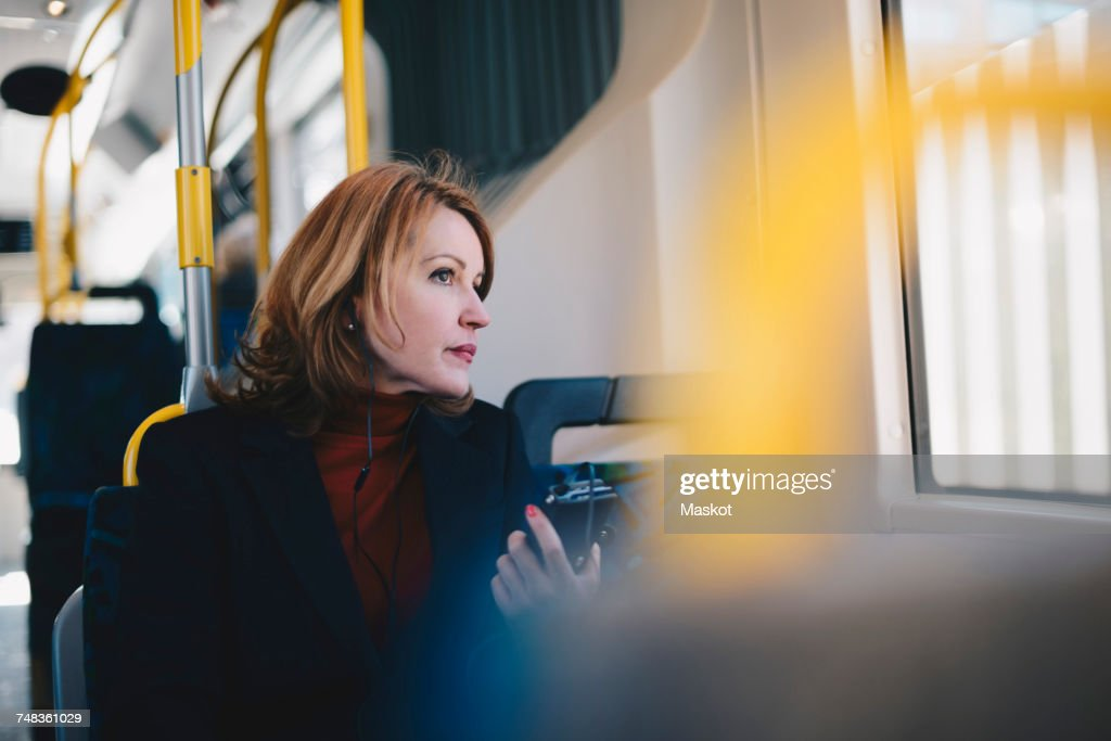 Woman wearing headphones listening music through mobile phone while traveling in bus : Stock Photo