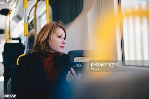 Woman wearing headphones listening music through mobile phone while traveling in bus