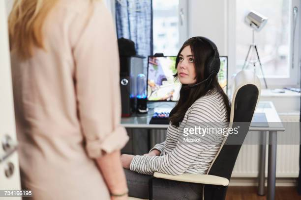 Woman wearing headphones looking at mother while sitting by desktop PC at home