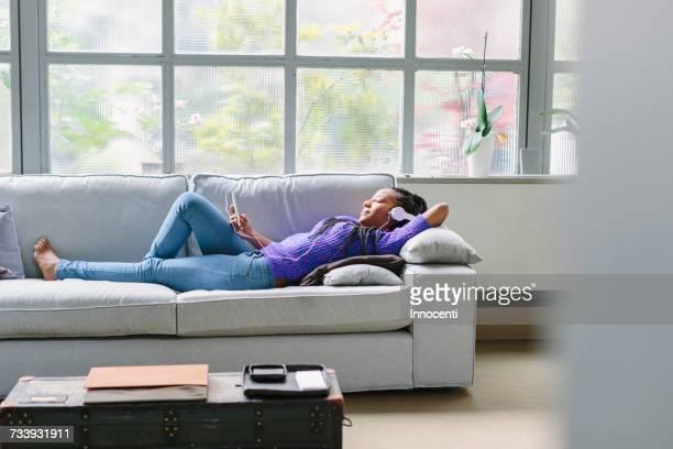 woman wearing headphones lying down on sofa - florence douillet photos et images de collection