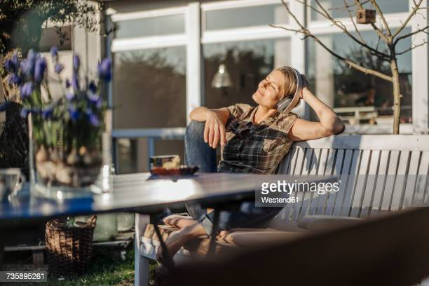 woman wearing headphones relaxing on garden bench - zen like stock pictures, royalty-free photos & images