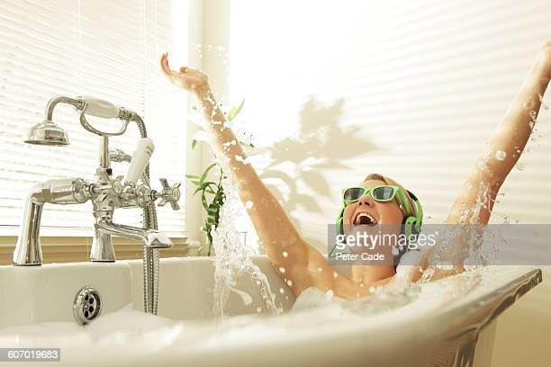 Woman wearing headphones splashing in bath