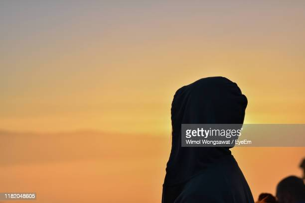 woman wearing headscarf against sky during sunset - wimol wongsawat stock photos and pictures