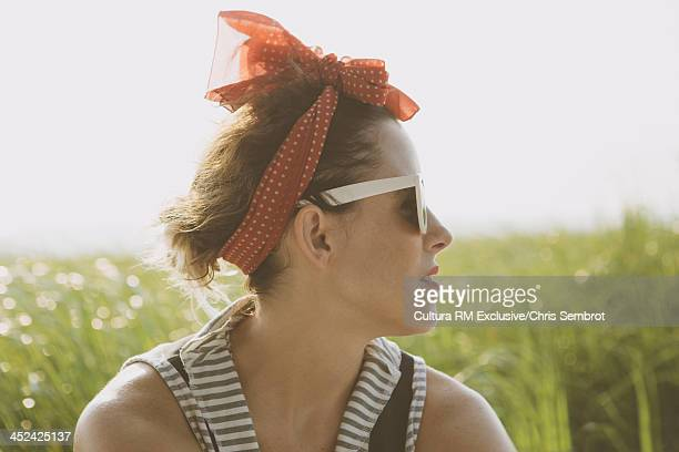 Woman wearing headscarf and sunglasses looking away