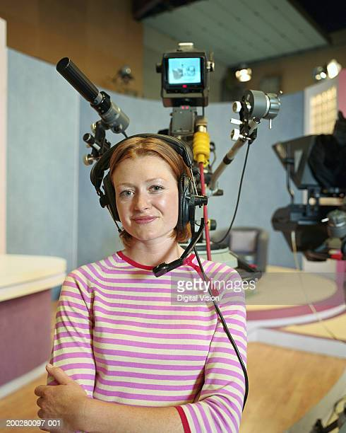 Woman wearing headset in television studio, smiling, portrait