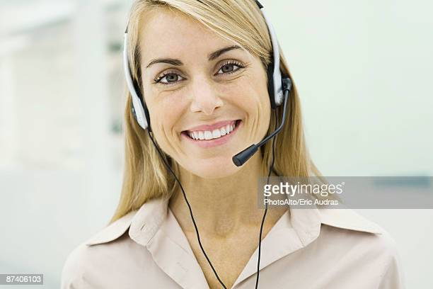 Woman wearing headset, smiling at camera, portrait