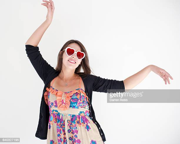 Woman wearing heart shape sunglasses dancing