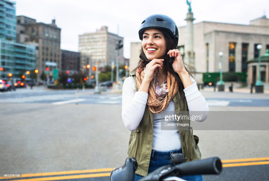 Woman wearing helmet while standing with bicycle in city : Stock Photo