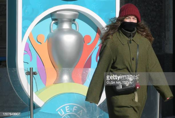 A woman wearing her scarf wrapped around her face walks past the Euro 2020 countdown clock displaying 449 days left before the event in downtown...