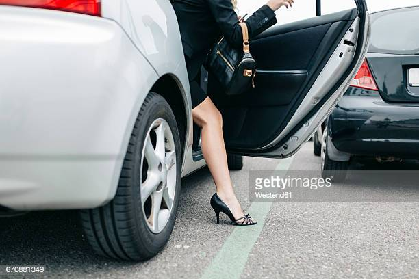 woman wearing high heels getting out of car - high heels short skirts stock photos and pictures