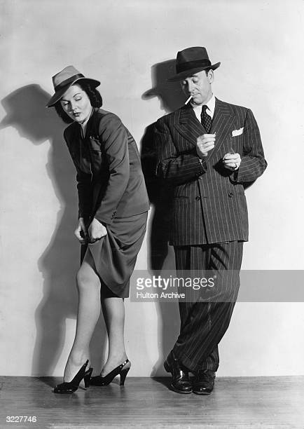 A woman wearing high heels lifts her skirt to adjust her stocking as a man next to her peers at her leg He is lighting a cigarette