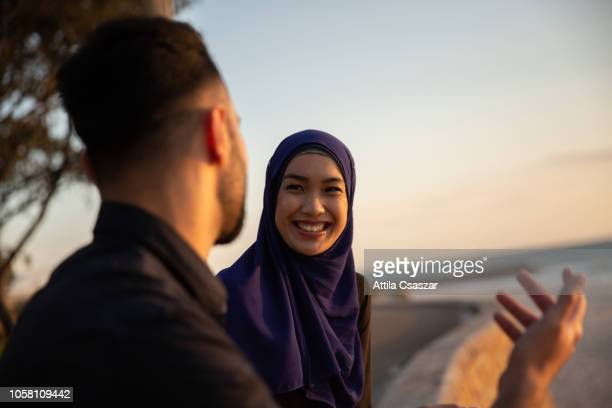 woman wearing hijab talking with friend at beach at sunset - zurückhaltende kleidung stock-fotos und bilder