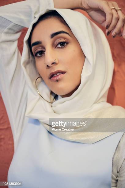 Woman wearing hijab with arm over head