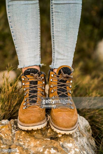 Woman wearing hiking boots standing on a rock