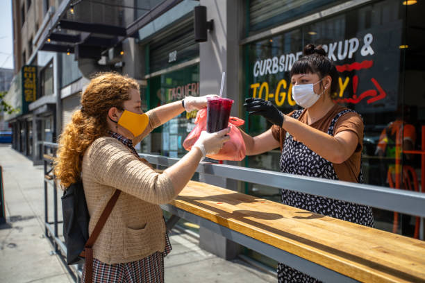 la femme utilisant le masque fait maison ramasse la nourriture au restaurant pendant le verrouillage de covid-19 - entreprise aux etats unis photos et images de collection