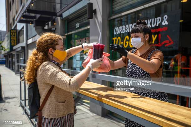 woman wearing homemade mask picks up food at restaurant during covid-19 lockdown - restaurant stock pictures, royalty-free photos & images