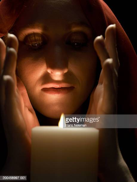 Woman wearing hood, cupping hands in front of candle, close-up