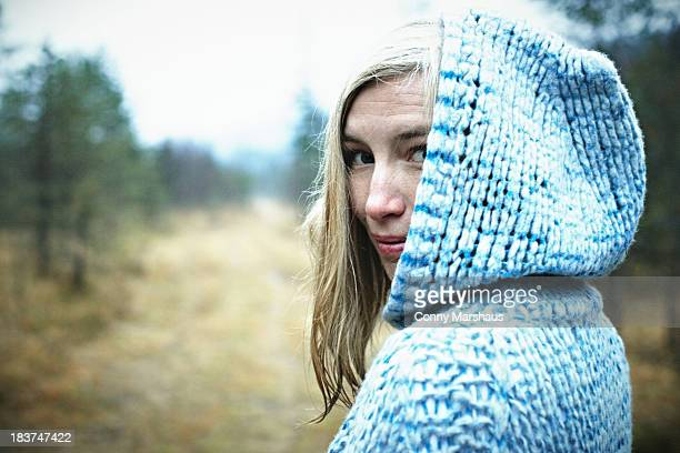 Woman wearing hooded top in forest