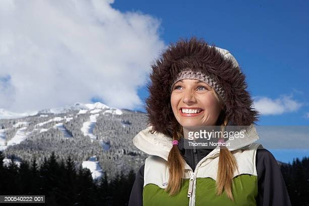Woman wearing hooded vest beside snow-covered mountain, looking up