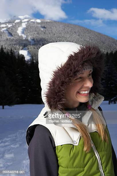 Woman wearing hooded vest outdoors in snow, looking away, smiling
