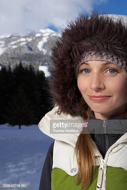 Woman wearing hooded vest outdoors in snow, portrait