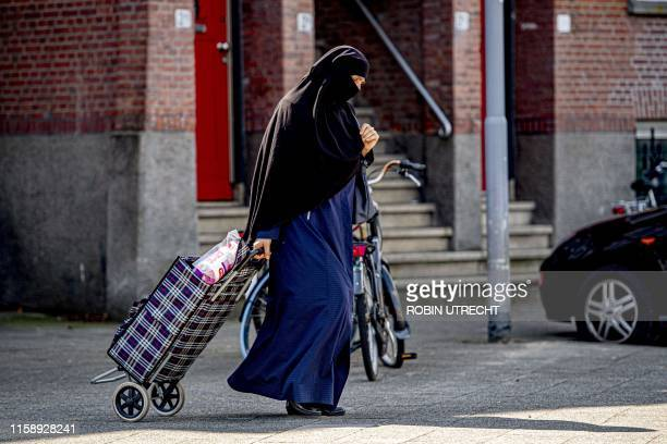 Woman wearing Islamic dress pulls a shopping trolley along a street in Rotterdam on July 29, 2019. - The Netherlands banned the wearing of a...
