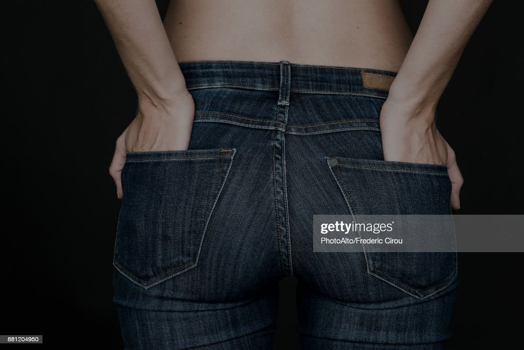 Woman wearing jeans, hands in back pockets : Stock Photo