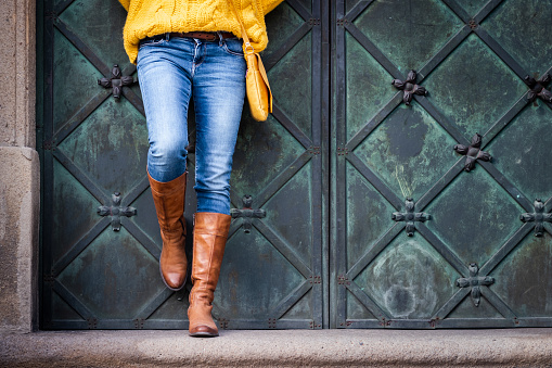 Woman wearing jeans, knitted sweater and leather boots is leaning at ancient gate. 1167233409