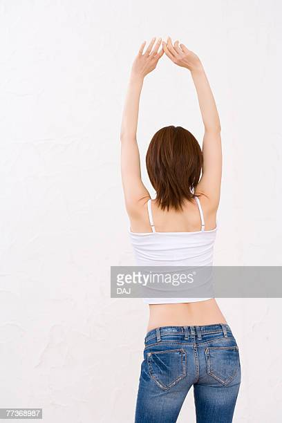Woman wearing jeans, stretching arms above head, rear view