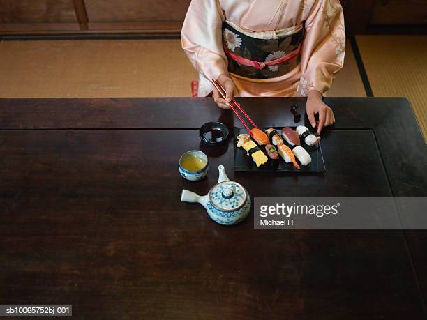 woman wearing kimono eating sushi, high angle view - cerimónia imagens e fotografias de stock