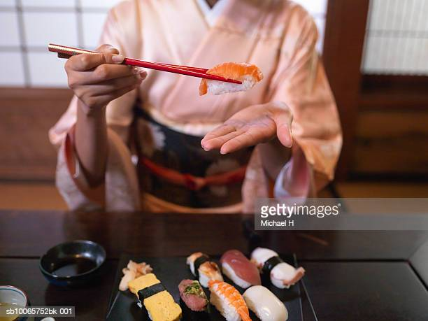 Woman wearing kimono eating sushi with chopsticks